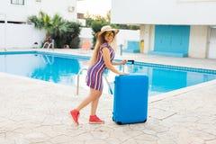 Glückliche junge Frau mit dem blauen Gepäck, das zum Erholungsort ankommt Sie geht nahe bei dem Swimmingpool Anfang von Lizenzfreies Stockfoto
