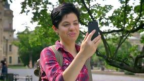 Glückliche junge Frau mit dem kurzen Haar, das Videochat durch das Telefon und Lächeln, stehend im Park nahe College, Student hat stock video