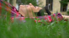 Glückliche junge Frau mit dem kurzen schwarzen Haar lächelnd und auf Gras liegend, nett und freundlich stock footage