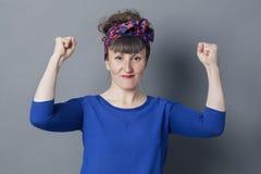 Glückliche junge Frau mit dem Retro- Blick, der ihre Arme für Sieg anhebt Stockbilder