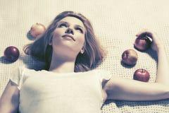 Glückliche junge Frau mit den Äpfeln, die auf dem Plaid im Freien liegen Stockfotos