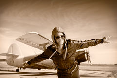 Glückliche junge Frau mit den angehobenen Händen, die auf airporte fliegen, Lizenzfreie Stockfotos