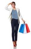 Glückliche junge Frau mit den Einkaufstaschen, die den Abstand untersuchen Stockbild