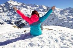 Glückliche junge Frau mit den Händen im schneebedeckten winte auf dem topof den Berg oben genießend Lizenzfreies Stockfoto