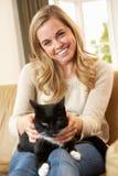 Glückliche junge Frau mit der Katze, die auf Sofa sitzt Lizenzfreie Stockfotos