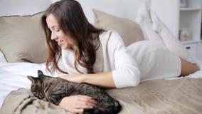 Glückliche junge Frau mit der Katze, die zu Hause im Bett isst stock video footage