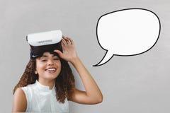Glückliche junge Frau mit der Spracheblase, die einen VR-Kopfhörer gegen grauen Hintergrund hält Stockbilder