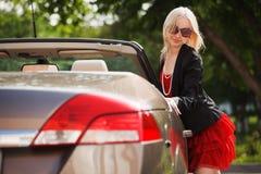 Glückliche junge Frau mit einem Auto Stockfoto
