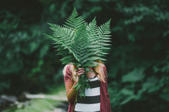 Glückliche junge Frau, mit Farnblatt in der grünen Natur Lizenzfreies Stockfoto