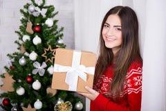 Glückliche junge Frau mit Geschenkbox und Weihnachtsbaum Stockbilder