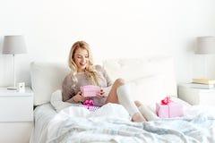 Glückliche junge Frau mit Geschenkboxen im Bett zu Hause Stockbild