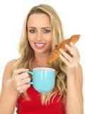 Glückliche junge Frau mit Kaffee und Hörnchen Stockfoto