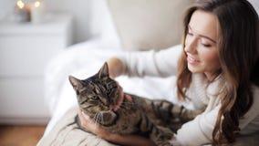 Glückliche junge Frau mit Katze im Bett zu Hause stock video