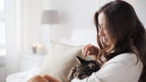 Glückliche junge Frau mit Katze im Bett zu Hause stock video footage