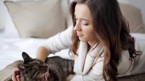 Glückliche junge Frau mit Katze im Bett zu Hause stock footage