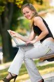 Glückliche junge Frau mit Laptop Lizenzfreie Stockfotografie