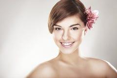 Glückliche junge Frau mit Orchidee Lizenzfreies Stockfoto