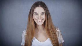 Glückliche junge Frau mit perfektem Lächeln lokalisiert auf grauem Hintergrund stock video