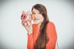 Glückliche junge Frau mit piggybank lizenzfreies stockfoto