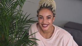 Glückliche junge Frau mit schönen Augen lächelnd nahe Blättern der Anlage im Raum stock footage