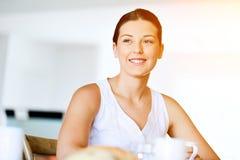 Glückliche junge Frau mit Tasse Tee oder Kaffee zu Hause Stockbilder