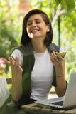 Glückliche junge Frau mit Telefon und Laptop lizenzfreies stockfoto
