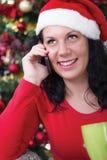 Glückliche junge Frau nahe dem Weihnachtsbaum, der Telefonanruf macht stockfotos