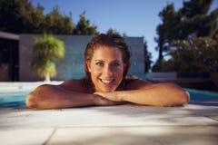 Glückliche junge Frau am Rand eines Swimmingpools Stockfotos