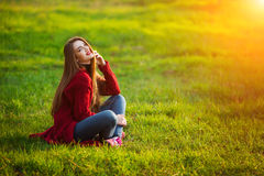 Glückliche junge Frau Schöne Frau mit dem langen gesunden Haar Sonnenlicht im Park genießend, der auf grünem Gras sitzt Frühling Lizenzfreie Stockbilder