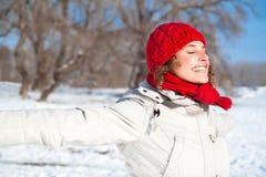 Glückliche junge Frau am sonnigen Tag des Schnees lizenzfreie stockfotos