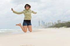 Glückliche junge Frau springt auf den Strand Lizenzfreies Stockbild