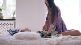 Glückliche junge Frau springt und kitzelt Freundin und sie sind lachendes Lügen des Spaßes auf einem Bett am Morgen stock video footage