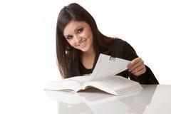 Glückliche junge Frau studiert ein Buch Stockfotografie