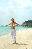 Glückliche junge Frau tanzt auf den Strand Glücklicher Lebensstil Weißer Sand, blauer Himmel Stockbilder