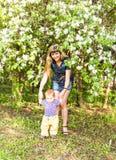 Glückliche junge Frau und kleiner Sohn im blühenden Frühling arbeiten im Garten Muttertagesfeiertagskonzept lizenzfreies stockfoto