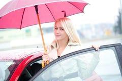 Glückliche junge Frau und rotes Auto Stockfotos