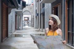 Glückliche junge Frau verlor in der Stadtholdingkarte Touristisches asiatisches Mädchen der Reise mit Karte Reise-Reise-Konzept stockfotografie