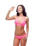 Glückliche junge Frau in wellenartig bewegender Hand des rosa Badeanzugs Stockbild