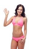 Glückliche junge Frau in wellenartig bewegender Hand des rosa Badeanzugs Stockfotos