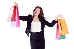 Glückliche junge Frau zeigt Taschen mit Käufen Lizenzfreie Stockbilder