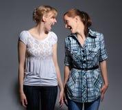 Glückliche junge Frau zwei, die auf grauem Hintergrund steht Stockfotografie