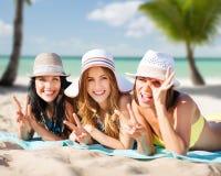Glückliche junge Frauen in den Bikinis auf Sommer setzen auf den Strand Lizenzfreie Stockfotos
