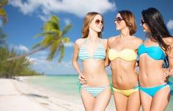 Glückliche junge Frauen in den Bikinis auf Sommer setzen auf den Strand Stockbild
