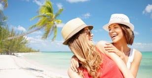 Glückliche junge Frauen in den Hüten auf Sommer setzen auf den Strand Lizenzfreie Stockfotografie