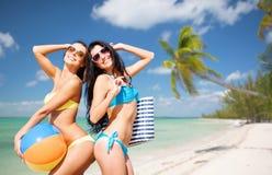 Glückliche junge Frauen im Bikini, der auf Sommer aufwirft, setzen auf den Strand Lizenzfreie Stockfotos