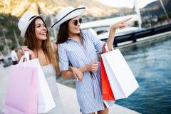 Glückliche junge Frauen mit Einkaufstaschen genießend im Einkaufen Verbraucherschutzbewegung, Einkaufen, Lebensstilkonzept lizenzfreies stockbild