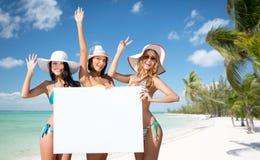 Glückliche junge Frauen mit weißem Brett auf Sommer setzen auf den Strand Lizenzfreie Stockfotografie