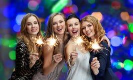 Glückliche junge Frauen mit Wunderkerzen über Lichtern Stockbilder