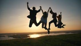 Glückliche junge Freunde, welche die Hände springen bei Sonnenuntergang auf dem Hügel anheben stock video footage