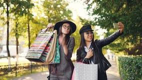 Glückliche junge Freundinnen nehmen selfie mit den Papiertüten, die draußen auf Bürgersteig und der Aufstellung stehen Mädchen ve stock footage